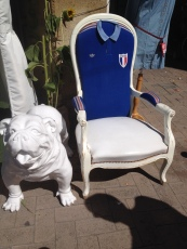 A chair upholstered with a French Rugby shirt outside a shop in the main square