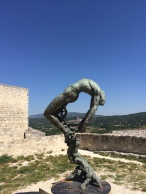 'Tree of Life' Sculpture by Ettore Greco on the terrace outside Lacoste Chateau, framing Bonnieux in the distance
